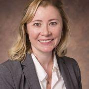 Headshot of blonde woman in grey blazer and white button down shirt